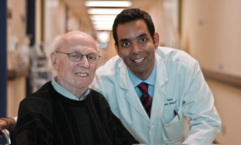 Photo Of Samir Sinha With Patient In Hallway Of Hospital